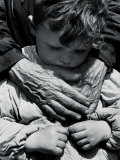 Child Dressed in a Preschool Pinafore with the Hands of an Elderly Woman Draped across His Chest