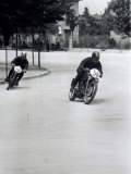 Two Motorcyclists Racing Along a Road  Otorcycles are Numbered 46 and 36