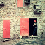 Woman with a Rabbit in Her Arms Leaning on the Jamb of a Door in a Stone Farmhouse
