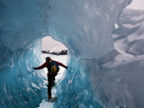 A hiker explores an ice cave recently revealed at Mendenhall Glacier