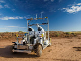 Astronauts test a surface transport vehicle in the Arizona desert