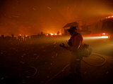A fireman watches flames advance down a hill toward local businesses