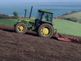 John Deere Tractor with a Rotivator on a Sloping Field in Spring  at Holcombe  Devon  England  UK