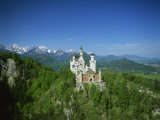 Neuschwanstein Castle on a Wooded Hill with Mountains in the Background  in Bavaria  Germany