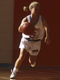 Female High School Basketball Player in Action During a Game