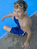 Portrait of 9 Year Old Boy Sitting at the Edge of the Swimming Pool  Kiamesha Lake  New York  USA