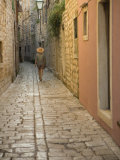 Woman walking in narrow cobblestone alley  Stari Grad Town  Hvar Island  Dalmatia  Croatia