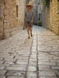Woman walking in narrow cobblestone alley  Stari Grad Town  Hvar Island  Dalmatia  Croatia