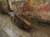 Chinese man pushing cart  Hong Cun Village  Yi County  China