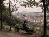 Woman Sits Atop a Hill Overlooking the Rooftops of the Kassel Town
