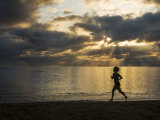 Silhouetted Woman Jogging on a Beach at Twilight
