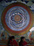 Two Young Buddhist Monks Seated under an Ornate Painting