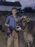 Teenager Proudly Holds His Winning Brown Swiss Cow and their Ribbons