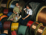 Employees Eat Lunch Amid Rolls of Wire and Cable at a Factory