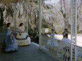Women Stand on Antebellum Mansion's Porch Framed by Belgian Ironwork