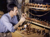Wood Carver Poses with His Mule Figurines
