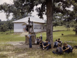 Schoolboys Sit in the Shade of a Tree Outside a Rural Schoolhouse