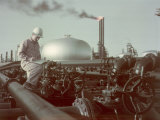 Oil Worker Records Data While Standing Amid Refinery Equipment