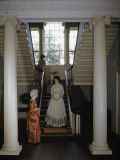 Three Women Wearing Colonial Dresses Stand in an Old Mansion