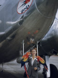 Flight Attendant Stands in Front of an Airplane with Two Macaws