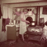 Woman Stands at Old-Fashioned Stove to Cook  Cats Prowl at Her Feet