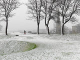Lone Figure Walking in Copenhagen Fortress During Snowstorm
