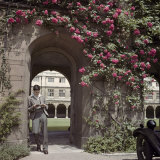 Student Stands in Cloister Arch Below Climbing Red Roses