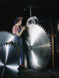 Factory Worker Inspects Notches of a Large Steel Saw Blade