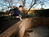 Jack Belle  a Traceur Vaulting a Wall Using Parkour in Urban Jungle