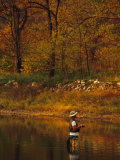 Man Standing in Calm Water Trying His Luck Fishing
