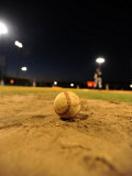 Baseball on a Dirt Mound During a Night Game