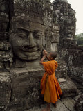 Young Buddhist Monk Prays at a Relief Statue of Buddha