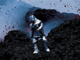 Scientist in a Thermal Suit and Helmet Collects Samples of Lava