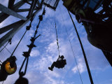 Worker Returns to Earth after Lubricating the Top of a Drilling Rig
