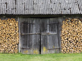 Barn Door Surrounded by Firewood Stacks