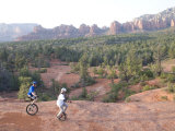 Two Men on Unicycles Ride a Rocky Ridge in the Arizona Desert