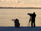 Silhouetted Hunter with Rifle and Photographer with Tripod Set Up