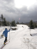 Woman Cross Country Skiing Along a Ridge Trail