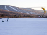 Man Tows Two Young Boys Behind a Kite across a Frozen Lake