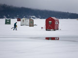 Ice Fisherman with a Drill Walking Among Fishing Shacks on a Frozen Lake