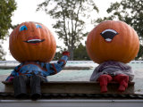 Painted Pumpkin Figures Wave from the Roof of a Roadside Stand