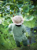 Person Wearing a Straw Hat Standing Near a Pond of Water Lilies
