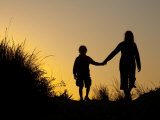 Seven Year Old Boy and His Mom Walk Hand in Hand Through Sand Dunes