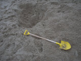 Child&#39;s Shovel and Hole in the Sandy Beach