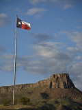 Texas Flag and Rugged Landscape in the Distance