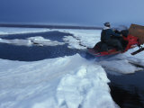 Man on a Snowmobile Jumping an Water-Filled Crack in the Ice