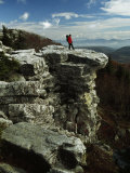 Hiker Standing at the Edge of a Rock Outcrop on a Cliff