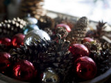 Bowl of Christmas Balls and Pine Cones Sit in a Window
