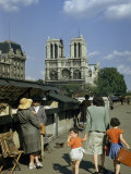 Mother Hurries Children Past Book Stalls Near Notre Dame De Paris