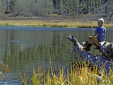 Boy Sits on a Log Trout Fishing in Grass Lake